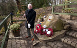Tony Foulds holds a broom as he stands next to a memorial honouring 10 U.S. airmen who died in a plane crash in Endcliffe Park, Sheffield, England, Wednesday, Feb. 13, 2019. Foulds was just a kid running around in the park when a U.S. Air Force crew decided to crash and die rather than take the chance of hitting them on Feb. 22, 1944. He's dreamed of honoring them for decades. Now he's 82 and about to get his wish. (AP Photo/Rui Vieira)