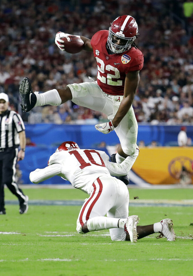 """File-This Dec. 29, 2018, file photo shows Alabama running back Najee Harris (22) jumping over Oklahoma safety Patrick Fields (10), during the first half of the Orange Bowl NCAA college football game, Saturday, Dec. 29, 2018, in Miami Gardens, Fla.  Harris is averaging 6.5 yards per carry in two seasons. """"We always like to have two or three guys at that position that can play,"""" Saban said. """"I think it keeps everybody fresh. It keeps everybody healthy rather than having one guy that's carrying the ball maybe a lot of turns every game and they get wore down as the season goes on. We've been fortunate to have three guys that have made a real impact at that position, different guys in different games."""" (AP Photo/Lynne Sladky, File)"""
