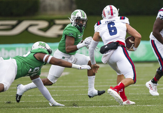 Marshall defensive tackle Jamare Edwards (99) and linebacker Tavante Beckett (4) attempt to bring down Florida Atlantic quarterback Nick Tronti (6) during an NCAA college football game on Saturday, Oct. 24, 2020, at Joan C. Edwards Stadium Huntington, W.Va. (Sholten Singer/The Herald-Dispatch via AP)