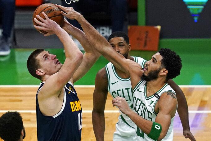Boston Celtics forward Jayson Tatum, right, blocks a shot by Denver Nuggets center Nikola Jokic, left, during the first half of an NBA basketball game, Tuesday, Feb. 16, 2021, in Boston. (AP Photo/Charles Krupa)
