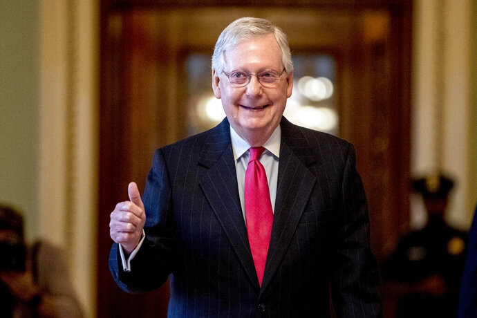 FILE - In this March 25, 2020, file photo, Senate Majority Leader Mitch McConnell, R-Ky. gives a thumbs up as he leaves the Senate chamber on Capitol Hill in Washington, where a deal has been reached on a coronavirus bill. Overwhelmed Kentucky and New York officials face a deluge of mail-in votes that are likely to delay results for days in high-profile congressional primaries on Tuesday, June 23. There's a lot of interest in two contests in particular. One involves former Marine combat pilot Amy McGrath's fight for the Democratic nomination to challenge Senate Majority Leader Mitch McConnell. (AP Photo/Andrew Harnik)