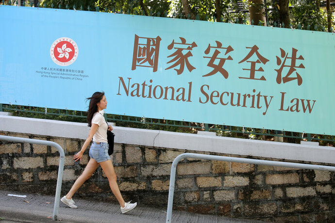 A woman walks past a promotional banner of the national security law for Hong Kong, in Hong Kong, Tuesday, June 30, 2020. China has approved a contentious law that would allow authorities to crack down on subversive and secessionist activity in Hong Kong, sparking fears that it would be used to curb opposition voices in the semi-autonomous territory. (AP Photo/Kin Cheung)