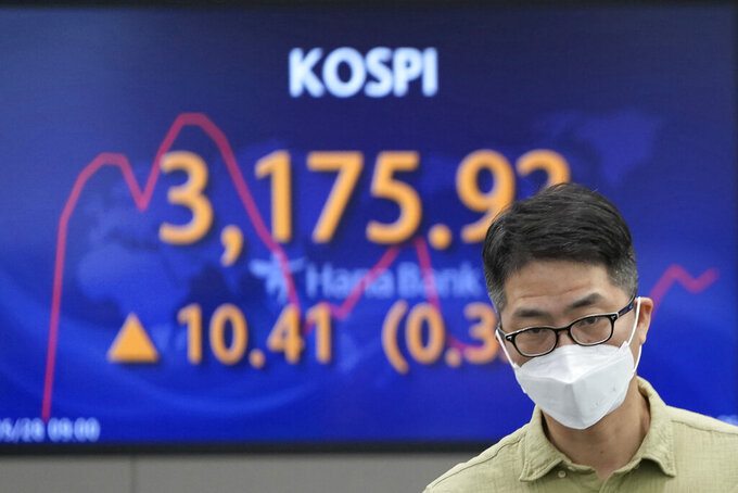 A currency trader walks near the screen showing the Korea Composite Stock Price Index (KOSPI) at the foreign exchange dealing room in Seoul, South Korea, Friday, May 28, 2021. Asian shares rose Friday, powered by encouraging signs that the U.S. economic recovery from the pandemic is gaining momentum. (AP Photo/Lee Jin-man)