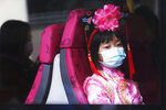 A girl wears a mask inside a bus in Hong Kong, Saturday, Jan. 25, 2020. China's most festive holiday began in the shadow of a worrying new virus Saturday as the death toll surpassed 40, an unprecedented lockdown kept 36 million people from traveling and authorities canceled a host of Lunar New Year events. (AP Photo/Achmad Ibrahim)