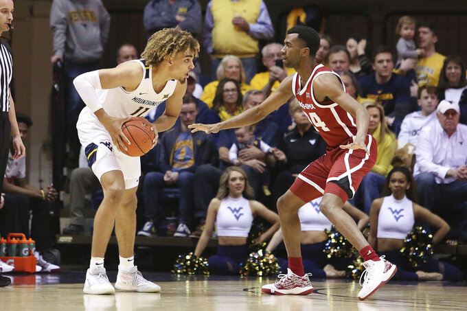 West Virginia forward Emmitt Matthews Jr. (11) looks to pass the ball while defended by Oklahoma guard Jamal Bieniemy (24) during the first half of an NCAA college basketball game Saturday, Feb. 29, 2020, in Morgantown, W.Va. (AP Photo/Kathleen Batten)