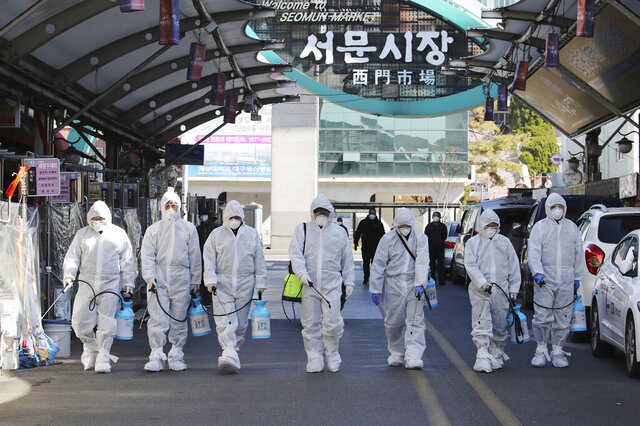 Workers wearing protective gears spray disinfectant as a precaution against the COVID-19 at a local market in Daegu, South Korea, Sunday, Feb. 23, 2020. South Korea's president has put the country on its highest alert for infectious diseases and says officials should take