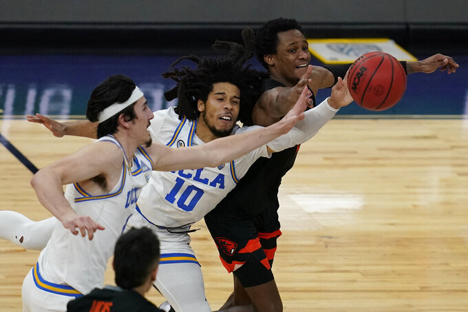 UCLA's Jaime Jaquez Jr., left, Tyger Campbell, center, and Oregon State's Gianni Hunt battle for the ball during the second half of an NCAA college basketball game in the quarterfinal round of the Pac-12 men's tournament Thursday, March 11, 2021, in Las Vegas. (AP Photo/John Locher)