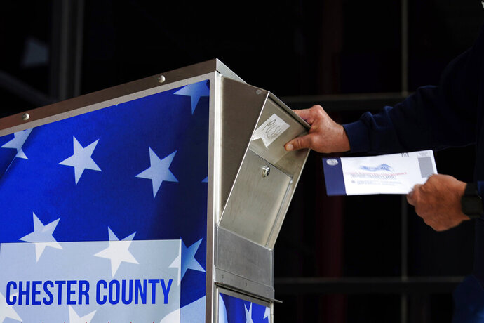 A man drops off his ballot for the 2020 General Election in the United States outside the Chester County Government Services Center, Friday, Oct. 23, 2020, in West Chester, Pa. (AP Photo/Matt Slocum)