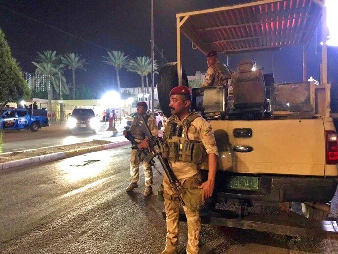Iraqi security forces stand guard near Bahraini embassy in Baghdad, Iraq, Thursday, June 27, 2019. Protesters stormed the Bahraini embassy compound in Baghdad Thursday night, removing the flag from above the building and replacing it with a Palestinian banner in protest against a conference held in the gulf nation to promote peace between Arabs and Israelis. (AP Photo/Ali Abdul Hassan)
