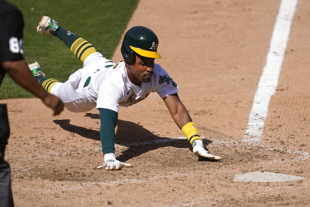 Oakland Athletics' Tony Kemp slides home to score against the Seattle Mariners during the seventh inning of a baseball game in Oakland, Calif., Sunday, Sept. 27, 2020. (AP Photo/Jeff Chiu)