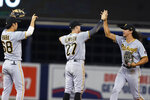 Pittsburgh Pirates shortstop Cole Tucker, right, celebrates with Kevin Newman (27) and Hoy Park (68) at the end of the team's baseball game against the Miami Marlins, Saturday, Sept. 18, 2021, in Miami. The Pirates won 6-3. (AP Photo/Marta Lavandier)