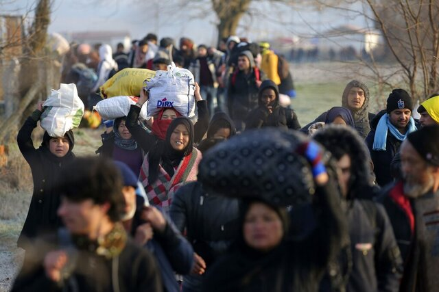 Migrants walk to reach Pazarakule border gate, Edirne, Turkey, at the Turkish-Greek border on Sunday, March 1, 2020. Turkey's President Recep Tayyip Erdogan said his country's borders with Europe were open Saturday, making good on a longstanding threat to let refugees into the continent as thousands of migrants gathered at the frontier with Greece. (AP Photo/Emre Tazegul)