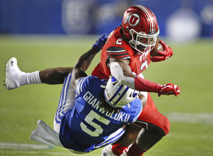 BYU defensive back Dayan Ghanwoloku (5) takes down Utah running back Zack Moss (2) in the second half during an NCAA college football game, Thursday, Aug. 29, 2019, in Provo, Utah. (AP Photo/George Frey)
