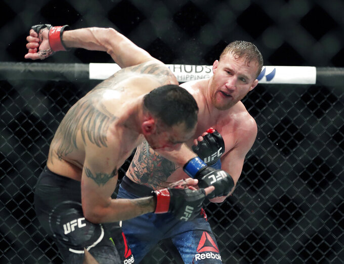 FILE - In this May 10, 2020, file photo, Tony Ferguson, left, falls backward after taking a punch from Justin Gaethje during a UFC 249 mixed martial arts boutin Jacksonville, Fla. Khabib Nurmagomedov will risk his unbeaten record and his UFC lightweight title against interim champion Gaethje in the main event of UFC 254 in Abu Dhabi on Saturday, Oct. 24, 2020. (AP Photo/John Raoux, File)