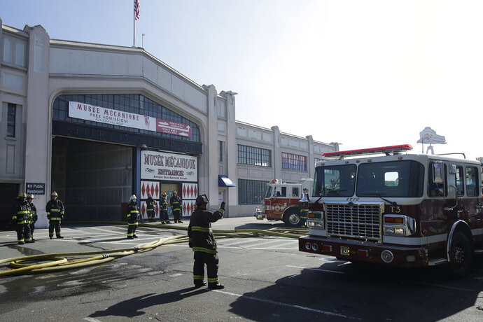Fire officials work in front of an entrance to Musee Mecanique after a fire broke out before dawn at Fisherman's Wharf in San Francisco, Saturday, May 23, 2020. A warehouse was destroyed. Fire officials said no injuries have been reported Saturday morning and firefighters are making multiple searches to ensure no one was inside the building on Pier 45. (AP Photo/Jeff Chiu)