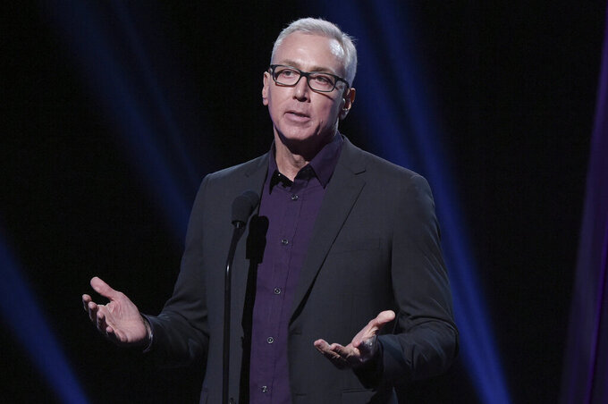 """FILE - This Jan. 18, 2019 file photo shows Drew Pinsky speaking at the 2019 iHeartRadio Podcast Awards in Burbank, Calif. Pinsky has apologized for a series of statements unspooled in a recent video where he downplayed the coronavirus and suggested that it was a """"press-induced panic."""" (Photo by Richard Shotwell/Invision/AP, File)"""