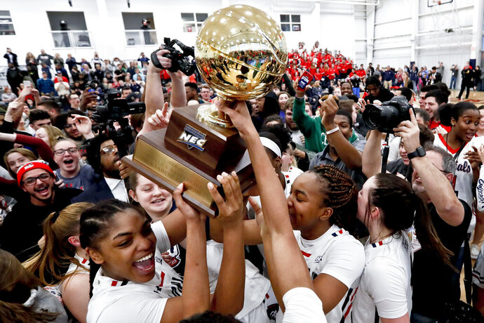 FILE - In this March 17, 2019, file photo, Robert Morris' Nneka Ezeigbo, left, holds the trophy as she celebrates with her teammates and fans after the team defeated St. Francis (Pa) in an NCAA college basketball game for the championship of the Northeast Conference women's tournament, in Moon, Pa. Robert Morris is leaving the Northeast Conference to join the Horizon League. The school announced on Monday, June 15, 2020, that it will become the 12th member of the Horizon League on July 1. (AP Photo/Keith Srakocic, FIle)