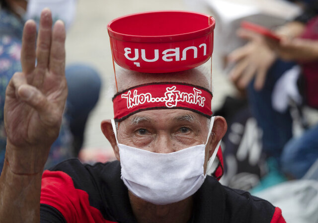 Pro-democracy supporter raises a three-finger salute, a symbol of resistance, with words on his head reading