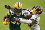 Green Bay Packers' Jamaal Williams pushes off Tampa Bay Buccaneers' Devin White during the second half of the NFC championship NFL football game in Green Bay, Wis., Sunday, Jan. 24, 2021. (AP Photo/Matt Ludtke)