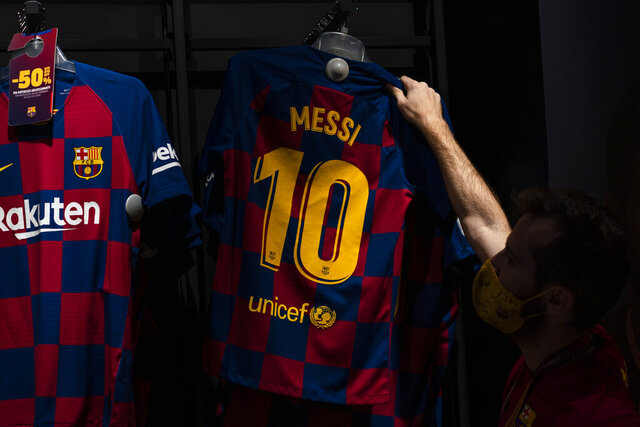 A worker holds a shirt with the name of Barcelona soccer player Lionel Messi at a F.C Barcelona store in Barcelona, Spain on Tuesday, Sept. 1, 2020. Barcelona is banking on a face-to-face meeting with Lionel Messi to try to convince him to stay. Talks with Messi's father-agent are expected this week in Barcelona but the club also hopes to sit down with the player himself.(AP Photo/Emilio Morenatti)
