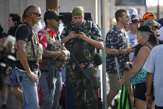 FILE - In this June 20, 2020 file photo, gun-carrying men wearing Hawaiian print shirts associated with the boogaloo movement watch a demonstration near where President Trump had a campaign rally in Tulsa, Okla. People following the anti-government boogaloo movement, which promotes violence and a second U.S. civil war, have been showing up at protests across the nation armed and wearing tactical gear. But the movement has also adopted an unlikely public and online symbol: Hawaiian print shirts.  (AP Photo/Charlie Riedel, File)