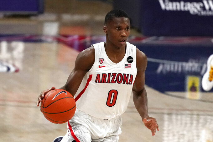 FILE - In this Jan. 7, 2021, file photo, Arizona guard Bennedict Mathurin brings the ball up during the first half of the team's NCAA college basketball game against Southern California in Tucson, Ariz. Mathurin is one of several key returning players who should help ease Tommy Lloyd's transition to head coach for the first time. Mathurin averaged 10.8 points as a freshman last season. (AP Photo/Rick Scuteri, File)