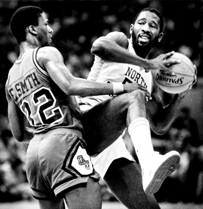 FILE - In this March 29, 2020, file photo, North Carolina forward James Worthy, right, keeps the ball away from Eric Smith of Georgetown during the NCAA college basketball Final Four championship game in New Orleans. Worthy won the duel of dunks with Georgetown's Pat Ewing, scoring a career-high 28 points and winning the Most Outstanding Player award. (Brian Smith/The Times-Picayune/The New Orleans Advocate, File)
