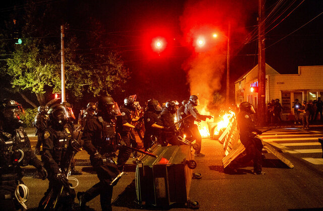 Police officers pass a fire lit by protesters on Saturday, Sept. 5, 2020, in Portland, Ore. Hundreds of people gathered for rallies and marches against police violence and racial injustice Saturday night in Portland, Oregon, as often violent nightly demonstrations that have happened for 100 days since George Floyd was killed showed no signs of ceasing. (AP Photo/Noah Berger)