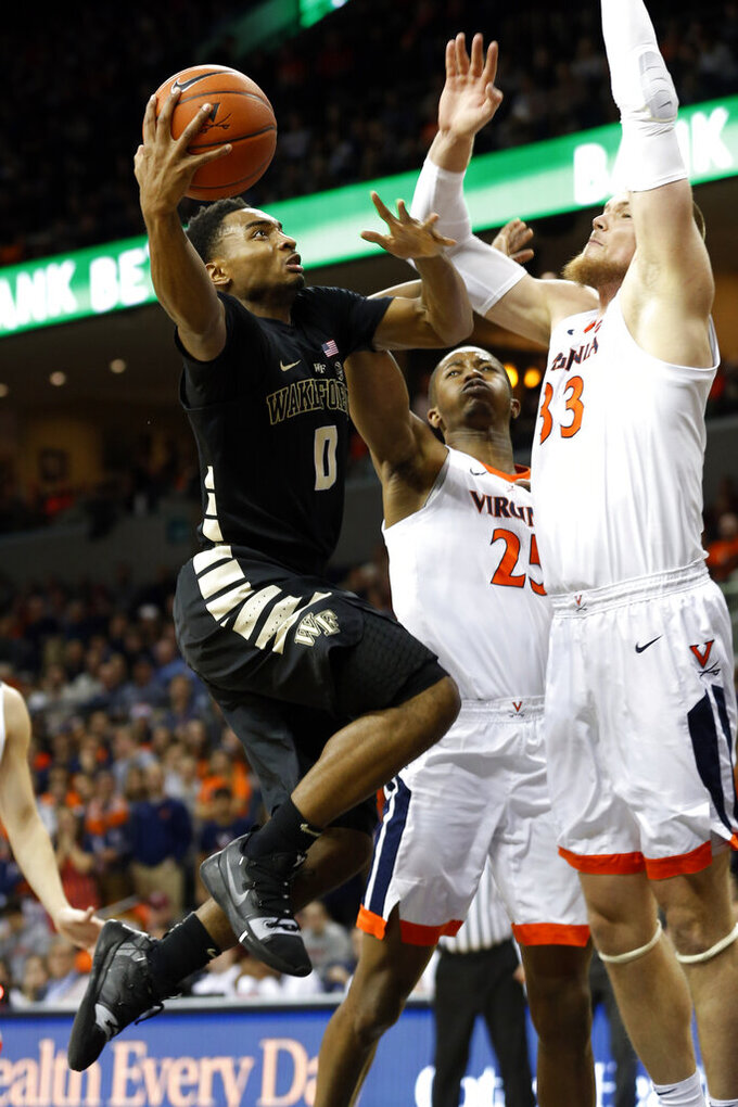 Wake Forest guard Brandon Childress (0) tries to get a shot off as Virginia center Jack Salt (33) and Virginia forward Mamadi Diakite (25) defend during the first half of an NCAA college basketball game in Charlottesville, Va., Tuesday, Jan. 22, 2019. (AP Photo/Steve Helber)