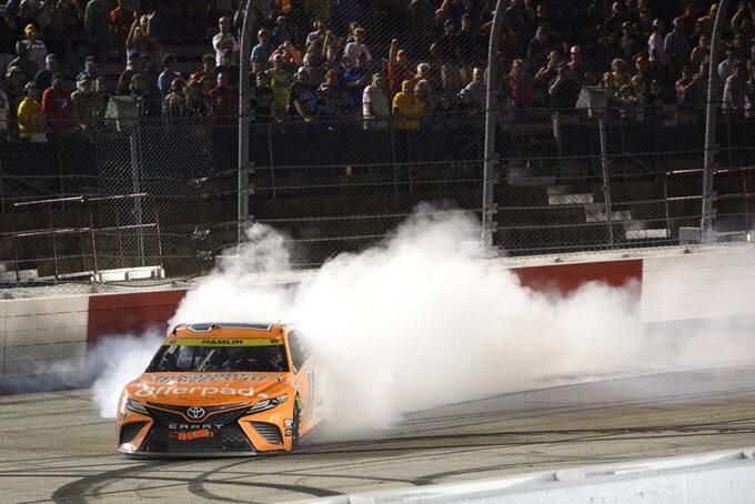 Denny Hamlin does a burnout after winning a NASCAR Cup Series auto race Sunday, Sept. 5, 2021, in Darlington, S.C. (AP Photo/John Amis)