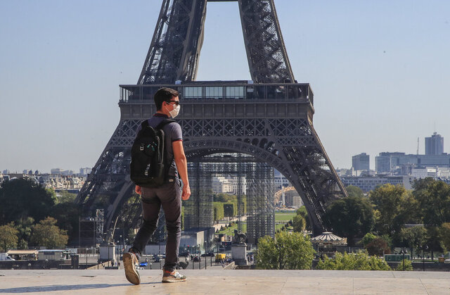 A man wearing protective a face mask as precaution against the conoravirus walk at Trocadero plaza near Eiffel Tower in Paris, Monday, Sept. 14, 2020. France sees a substantial increase of Covid-19 cases. (AP Photo/Michel Euler)
