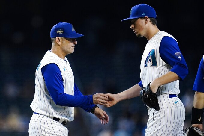 Arizona Diamondbacks manager Torey Lovullo, left, takes the ball from relief pitcher Taylor Clarke, right, during the 11th inning of a baseball game against the Seattle Mariners, Sunday, Sept. 5, 2021, in Phoenix. (AP Photo/Ross D. Franklin)
