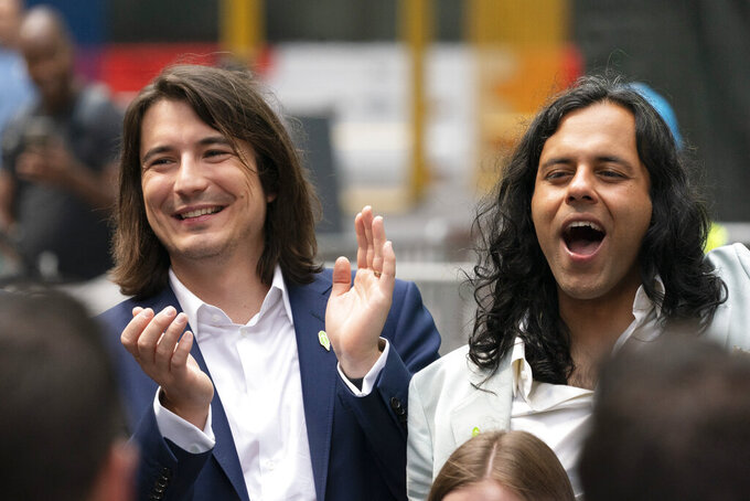 Vladimir Tenev, CEO and Co-Founder of Robinhood, left, celebrates in New York's Times Square with fellow Co-Founder Baiju Bhatt following their company's IPO, Thursday, July 29, 2021. Robinhood is selling its own stock on Wall Street, the very place the online brokerage has rattled with its stated goal of democratizing finance. Through its app, Robinhood has introduced millions to investing and reshaped the brokerage industry, all while racking up a long list of controversies in less than eight years. (AP Photo/Mark Lennihan)