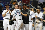 Florida Marlins players celebrate after Jazz Chisholm Jr. (2) scored the winning run during the 10th inning of a baseball game against the Washington Nationals, Monday, Sept. 20, 2021, in Miami. (AP Photo/Marta Lavandier)