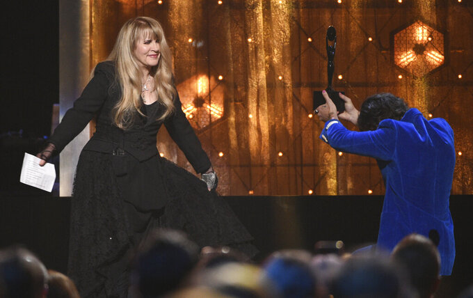 """FILE - Harry Styles, right, presents a trophy to Stevie Nicks at the Rock & Roll Hall of Fame induction ceremony in New York on March 29, 2019. Nicks has become close friends when the former One Direction member since he invited her to perform at one of his concerts in 2017. Since then, they're performed several times together and Styles even previewed his latest album, """"Fine Line,"""" for her and some of her friends before it was released in December. (Photo by Evan Agostini/Invision/AP, File)"""
