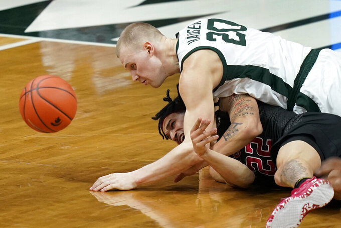 Michigan State forward Joey Hauser (20) falls on Rutgers guard Caleb McConnell (22) as they chase the loose ball during the first half of an NCAA college basketball game, Tuesday, Jan. 5, 2021, in East Lansing, Mich. (AP Photo/Carlos Osorio)