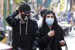 People wear protective face masks to help prevent the spread of the coronavirus in downtown Tehran, Iran, Sunday, Oct. 11, 2020. Iran announced on Sunday its highest single-day death toll from the coronavirus with 251 confirmed dead, the same day local media reported two senior officials had been infected and the nation's currency plunged to its lowest level ever. (AP Photo/Ebrahim Noroozi)