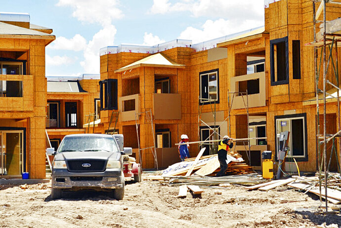 FILE - In this July, 2013 file photo, construction workers erect the Ledgestone Apartments in east Hobbs, N.M. The construction job boom continues in New Mexico thanks in large part to the oil and gas boom in the southeastern corner of the state, according to the Associated General Contractors of America. (The Hobbs Daily News-Sun via AP, File)