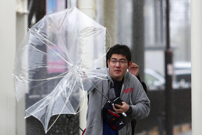 A man struggles with his umbrella against strong wind as Typhoon Hagibis approaches Suzuka, central Japan, Saturday, Oct. 12, 2019. Tokyo and surrounding areas braced for a powerful typhoon forecast as the worst in six decades, with streets and trains stations unusually quiet Saturday as rain poured over the city. (AP Photo/Toru Takahashi)