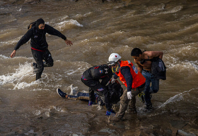Paramedics and demostrators attend a youth who fell into the Mapocho river from a bridge during a police charge on protesters in Santiago, Chile, Friday Sept.2, 2020. The incident unleashed a wave of criticism against police for the repression during demonstrations and the government repudiated the acts of violence condemning