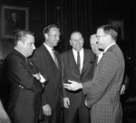 FILE - In this Oct. 11, 1956, file photo, from left, Art Modell, president of the Cleveland Browns; Peter Rozelle, National Football League commissioner; Tex Schramm, Dallas Cowboys president; Milt Woodard, American Football League commissioner; and Lamar Hunt, president of the Kansas City Chiefs, talk before the start of a House Judiciary Subcommittee hearing in Washington. In the early days of the NFL, college football was king and playing the game professionally was not something most players aspired to do. By planting its flag in large cities, embracing television exposure and playing a more entertaining style, the NFL surged in popularity in the middle of the 20th century and turned college football into a means to an end for many players. (AP Photo/File)