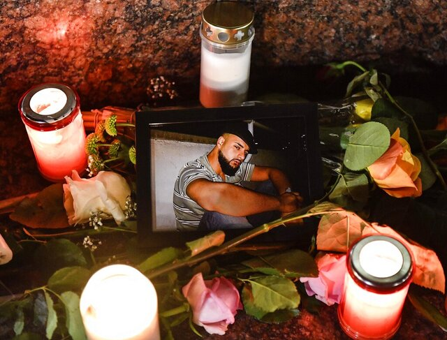 A photo is placed between candles and flowers at a monument after a vigil for the victims of the shooting in Hanau, Germany, Thursday, Feb. 20, 2020. A 43-year-old German man shot and killed several people at several locations in a Frankfurt suburb overnight in attacks that appear to have been motivated by far-right beliefs, officials said Thursday. (AP Photo/Martin Meissner)