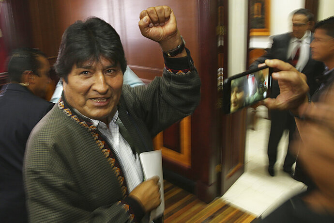 Bolivia's former President Evo Morales pumps his fist after a press conference at the journalists club in Mexico City, Wednesday, Nov. 27, 2019. Morales went into exile in Mexico after he was prodded by police and the military, forcing him to resigned on Nov. 10, after he claimed victory in an election that international observers invited in by the government said was marred by numerous irregularities. (AP Photo/Marco Ugarte)
