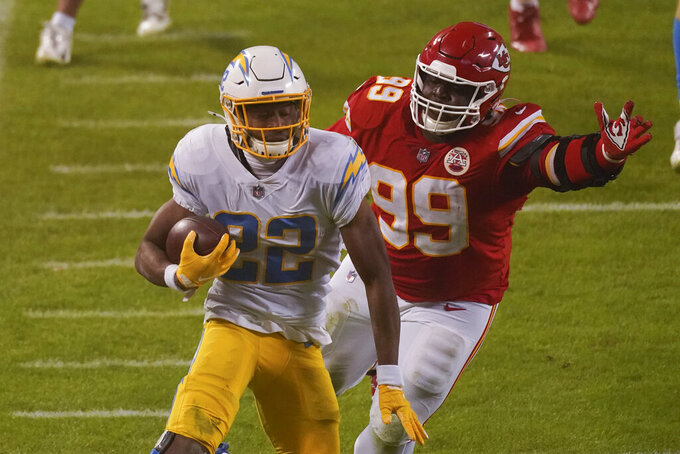 Los Angeles Chargers running back Justin Jackson runs from Kansas City Chiefs defensive tackle Khalen Saunders (99) during the second half of an NFL football game, Sunday, Jan. 3, 2021, in Kansas City. (AP Photo/Charlie Riedel)