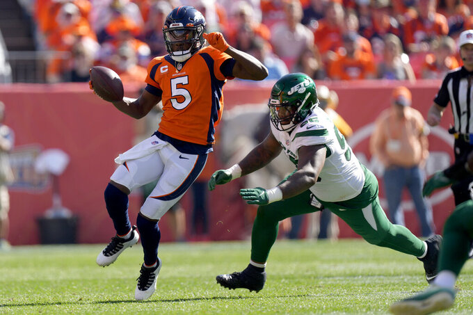 Denver Broncos quarterback Teddy Bridgewater (5) eludes the reach of New York Jets defensive tackle Quinnen Williams during the first half of an NFL football game, Sunday, Sept. 26, 2021, in Denver. (AP Photo/David Zalubowski)