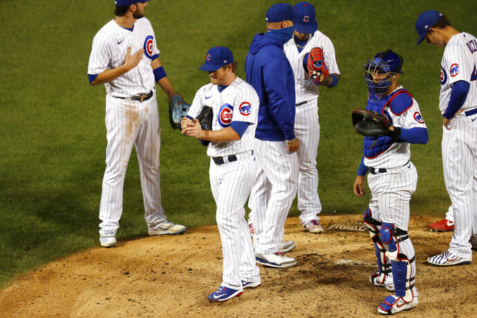 Chicago Cubs relief pitcher Craig Kimbrel, second from left, is taken out of the baseball game by manager David Ross during the ninth inning against the Kansas City Royals on Tuesday, Aug. 4, 2020, in Chicago. The Cubs won 5-4. (AP Photo/Charles Rex Arbogast)