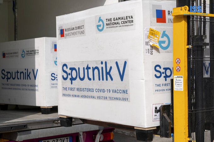 Boxes containing Russian vaccine Sputnik V are unloaded in San Marino, Tuesday, Feb. 23, 2021. The Republic of San Marino, a city state surrounded by Italy, is welcoming the arrival of the first 7,500 Russian Sputnik V coronavirus vaccines after its plans to get its doses from Italy got delayed. A pink and yellow truck escorted by police cars brought the vaccines across the frontier into San Marino on Tuesday. Eventually, officials said the Russian doses will be enough to vaccinate some 15% of the microstate's population of around 33,800. (Andrea Costa/IssRSMarino via AP)