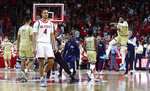Georgia Tech's James Banks III, right, and the team celebrate as North Carolina State's Jericole Hellems (4) walks off the court after Tech's 82-81 overtime victory in an NCAA college basketball game at PNC Arena in Raleigh, N.C., Tuesday, Nov. 5, 2019. (Ethan Hyman/The News & Observer via AP)