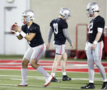 Ohio State quarterback Justin Fields, left, takes a snap in front of teammates quarterback Daniel Vanatsky, center, and quarterback Matthew Baldwin during an NCAA college football practice in Columbus, Ohio, Wednesday, March 6, 2019. (AP Photo/Paul Vernon)