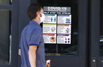 A pedestrian wears a face mask while passing by a sign placed on the door of a business in an effort to stop the rise of the new coronavirus Wednesday, May 20, 2020, in Denver. (AP Photo/David Zalubowski)